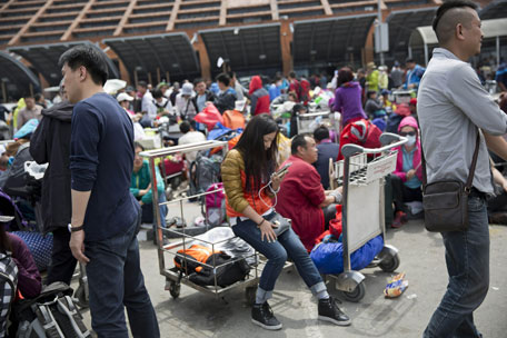 People wait to go inside the Kathmandu international airport, in Kathmandu, Nepal, Sunday, April 26, 2015. (AFP)