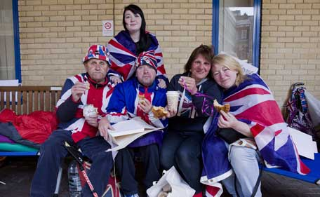 Royal fans pose eating pastries given to them by the Royal couple outside the Lindo Wing of St Mary's hospital in central London on April 28, 2015. The Duke and Duchess of Cambridge thanked ardent supporters camped outside the private maternity wing where their second child will be born by sending them two boxes of breakfast pastries and coffee. (AFP)
