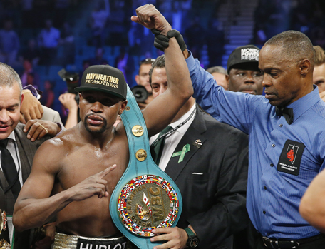 Floyd Mayweather Jr., celebrates his victory over Manny Pacquiao, from the Philippines, with the champion's belt following their welterweight title fight on Saturday, May 2, 2015 in Las Vegas. At right is referee Kenny Bayless. (AP)