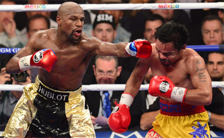 Floyd Mayweather Jr (left)  connects against Manny Pacquiao during their welterweight unification bout on May 2, 2015 at the MGM Grand Garden Arena in Las Vegas, Nevada. (AFP)