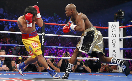 Floyd Mayweather Jr of the US goes after Manny Pacquiao (left) of the Philippines in the first round during their welterweight WBO, WBC and WBA (Super) title fight in Las Vegas, Nevada, May 2, 2015. (Reuters)