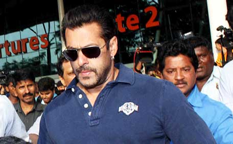 Indian Bollywood actor Salman Khan walks with officials as he arrives at an airport in Mumbai on May 5, 2015. (AFP)
