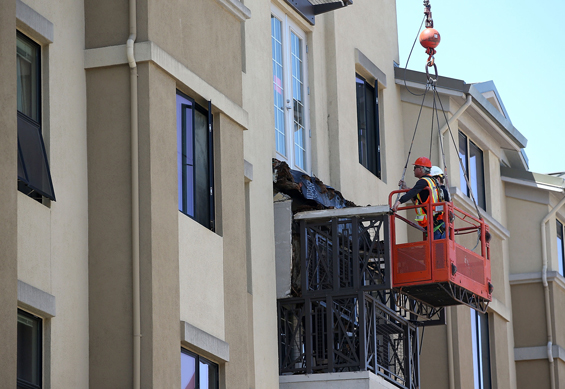 Workers inspect a balcony that collapsed at an apartment building near UC Berkeley on June 16, 2015 in Berkeley, California. (AP)