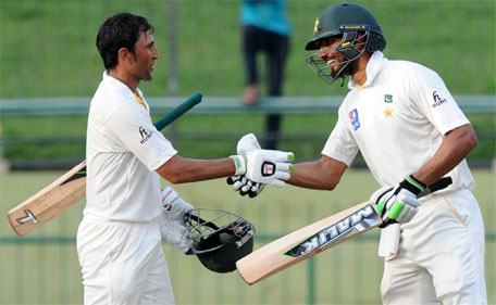 Pakistan cricketer Younis Khan (left) is congratulated by teammate Shan Masood after he scored a century during the fourth day of the third and final Test cricket match between Sri Lanka and Pakistan at the Pallekele International Cricket Stadium in Pallekele on July 6, 2015. (AFP)