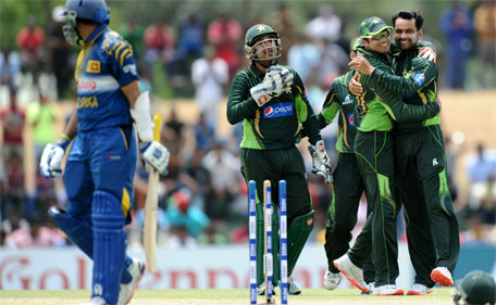 Pakistan cricketer Mohammad Hafeez (right) celebrates with teammates after he dismissed Sri Lankan batsman Tillekaratne Dilshan (left) during the first one day international cricket match between Sri Lanka and Pakistan at The Rangiri Dambulla International Cricket stadium in Dambulla, on July 11, 2015. (AFP)