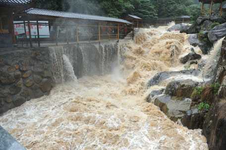 An overflowing river is seen during a heavy storm brought by typhoon Chan-hom in Lin'an, east China's Zhejiang province on July 11, 2015. (AFP)