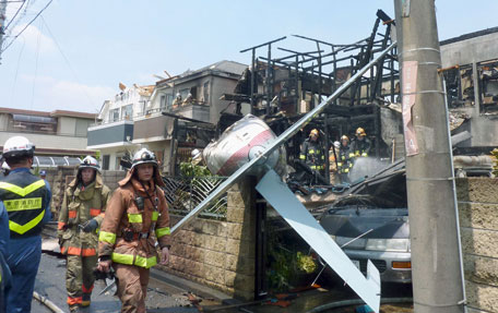 The tail section of a crashed light plane (C) and burning house are seen after the plane went down in a residential area and burst into flames, in Chofu, outskirt of Tokyo, in this photo taken by Kyodo July 26, 2015. A small airplane crashed into a residential area of the Japanese capital, Tokyo, on Sunday, setting fire to houses and cars and injuring at least two people, the Tokyo Fire Department said. Mandatory credit (REUTERS)