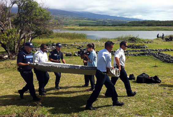 Police carry a piece of debris from an unidentified aircraft found in the coastal area of Saint-Andre de la Reunion, in the east of the French Indian Ocean island of La Reunion. (AFP)