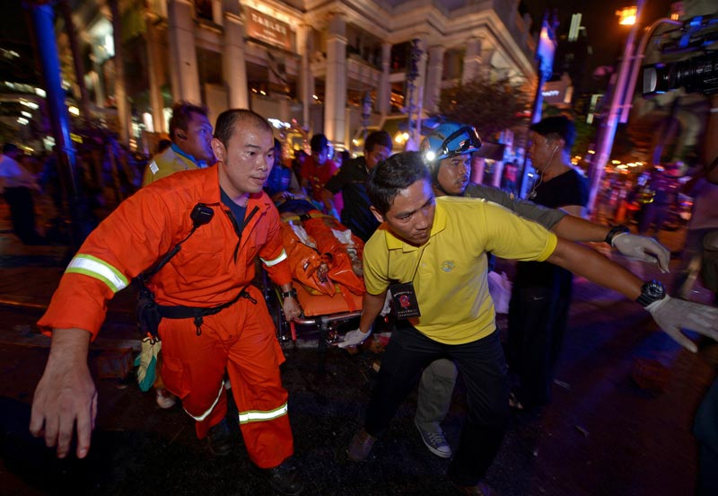 Thai rescue workers carry an injured person after a bomb exploded outside  shrine in central Bangkok late on August 17, 2015.  Body parts were scattered across the street after the explosion outside the Erawan Shrine in the downtown Chidlom district of the Thai capital. (AFP)
