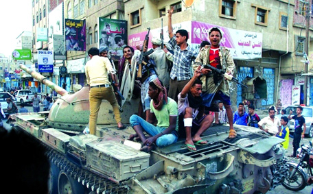 Militants loyal to Yemen's exiled government ride atop a tank they seized from Houthi militiamen in the country's central city of Taiz on August 17, 2015. (Reuters)