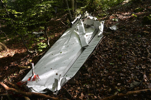 A part of the light aircraft that crashed near the village of Cerveny Kamen, Slovakia on Thursday, Aug. 20, 2015. Two planes carrying dozens of parachutists collided in midair over western Slovakia, killing several people, officials said. Slovak media reported more than a dozen other parachutists missing and an aviation official said some reportedly survived by jumping out with their parachutes (AP)