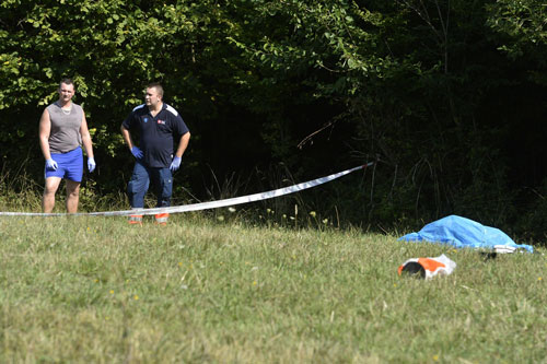 Rescuers stand next to the body of a skydiver who was killed in a plane crash near the village of Cerveny Kamen, Slovakia, Thursday, Aug. 20, 2015. Two planes carrying dozens of parachutists collided in midair over western Slovakia, killing several people, officials said. Slovak media reported more than a dozen other parachutists missing and an aviation official said some reportedly survived by jumping out with their parachutes (AP)