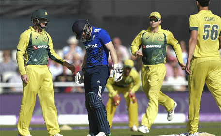 England's Eoin Morgan (second left) and Australian players react after Morgan was hit on the head by a ball during the fifth one day international (ODI) cricket match between England and Australia at Old Trafford in Manchester, northwest England, on September 13, 2015. (AFP)