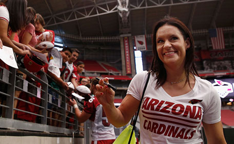 Intern linebacker coach Jen Welter of the Arizona Cardinals signs autographs following the team training camp at University of Phoenix Stadium on August 2, 2015 in Glendale, Arizona. (Getty Images)