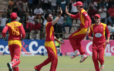 Zimbabwe players Chamunorwa Chibhabha (L) and a jumping  Graeme Cremer (R) celebrate a wicket in action during the first of two T20 cricket matches between Pakistan and hosts Zimbabwe at Harare Sports Club,  September 27, 2015. AFP