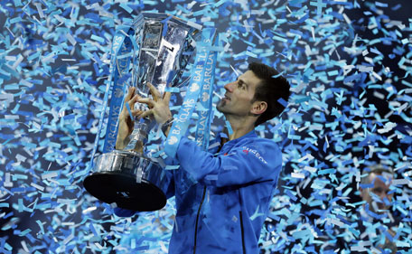 Novak Djokovic of Serbia holds up the winners trophy after he defeated Roger Federer of Switzerland in their singles final tennis match at the ATP World Tour Finals, in the O2 arena in London, Sunday Nov. 22, 2015. (AP