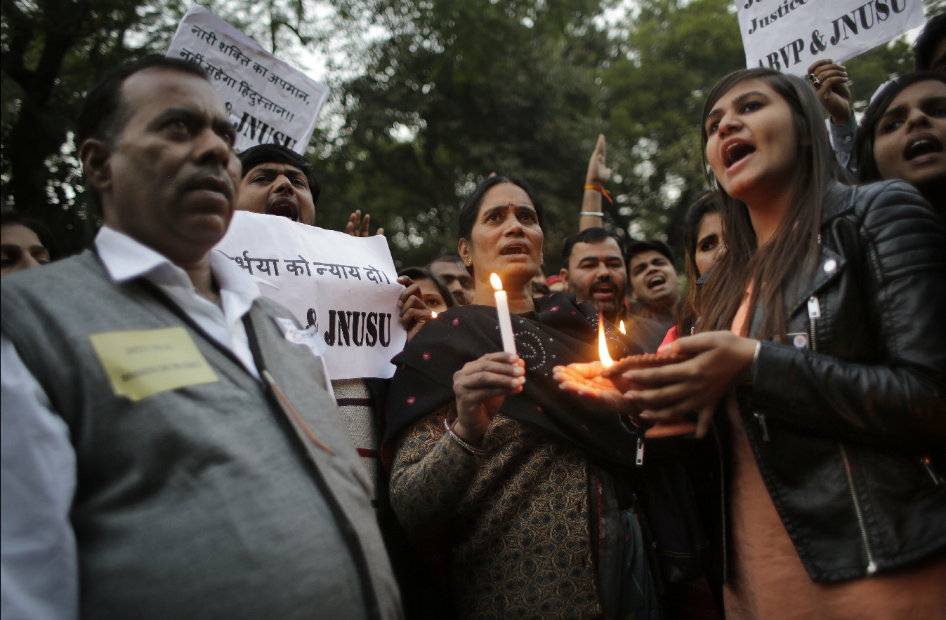 Father, left and mother, center of the Indian student victim who was fatally gang raped on this day three years back on a moving bus in the Indian capital join others at a candle lit vigil in New Delhi, India, Wednesday, Dec. 16, 2015. (AP)