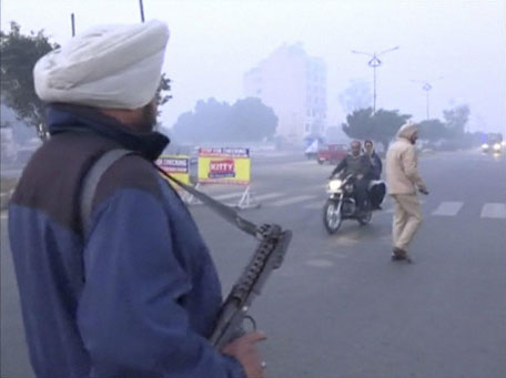 A policeman stands guard with a gun as vehicles pass by, following what officials said was an attack on an Indian Air Force base in Pathankot on Saturday, near the border with Pakistan, in Ludhiana, Punjab state, India, in this still frame taken from video, January 2, 2016. (Reuters)