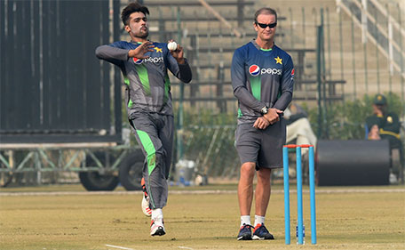 Pakistan cricket batting coach Grant Flower (right) watches as bowler Mohammad Amir delivers a ball during a team practice session at a camp ahead of the New Zealand tour, in Lahore on January 2, 2016. (AFP)