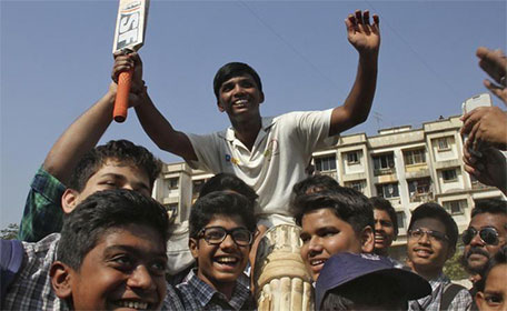 Schoolboy Pranav Dhanawade, 15, (centre) is lifted by children as they celebrate during an inter-school cricket tournament in Mumbai, January 5, 2016. (Reuters)