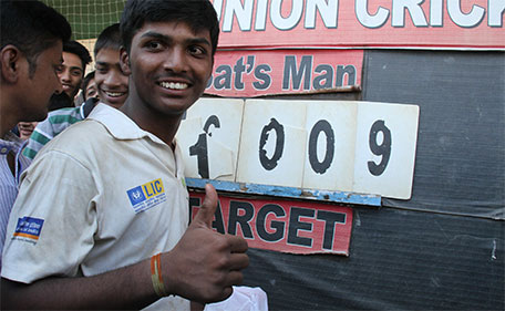 Mumbai schoolboy Pranav Dhanawade, 15, poses next to the score board after smashing a 117-year-old record for the highest number of runs scored in one innings in Mumbai on January 5, 2016. (AFP)