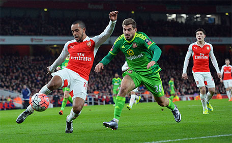 Arsenal's English striker Theo Walcott (left) plays the ball under pressure from Sunderland's Greek midfielder Charalampos Mavrias during the English FA Cup third-round football match between Arsenal and Sunderland at the Emirates Stadium in London on January 9, 2016. (AFP)