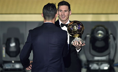 FC Barcelona and Argentina's forward Lionel Messi (right) holds his trophy as he shakes hands with Real Madrid and Portugal's forward  Cristiano Ronaldo after receiving the 2015 FIFA Ballon d'Or award for player of the year during the 2015 FIFA Ballon d'Or award ceremony at the Kongresshaus in Zurich on January 11, 2016. (AFP)