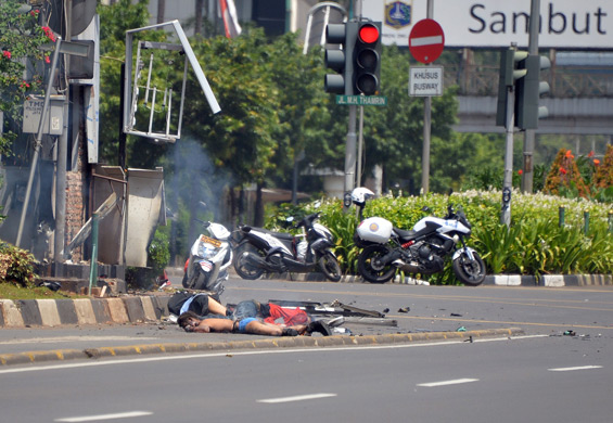 Three bodies lie on the street next to a damaged police post after a series of blasts hit the Indonesia capital Jakarta. (AFP)