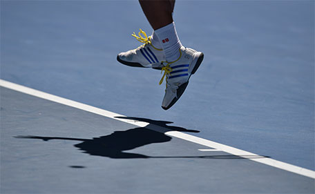 Serbia's Novak Djokovic casts a shadow on court as he serves during his men's singles match against South Korea's Chung Hyeon on day one of the 2016 Australian Open tennis tournament in Melbourne on January 18, 2016. (AFP)