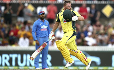 Australian batsman Aaron Finch takes his helmet off as he checks the ball he hit to reach a century during the team's One Day International cricket match against India in Canberra, Australia, Wednesday, Jan. 20, 2016. (AP)