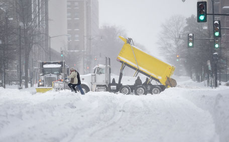 People negotiate crossing the street as workers clear snow, Saturday, Jan. 23, 2016, in Washington. A blizzard with hurricane-force winds brought much of the East Coast to a standstill Saturday, dumping as much as 3 feet of snow, stranding tens of thousands of travelers and shutting down the nation's capital and its largest city. (AP)