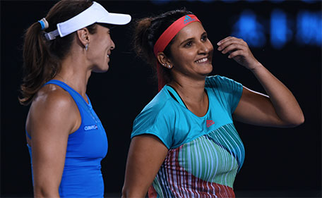 India's Sania Mirza (right) speaks with partner Switzerland's Martina Hingis during their women's doubles match against Germany's Julia Goerges and Czech Republic's Karolina Pliskova on day ten of the 2016 Australian Open tennis tournament in Melbourne on January 27, 2016. (AFP)