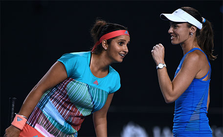 India's Sania Mirza (left) listens to partner Switzerland's Martina Hingis during their women's doubles match against Germany's Julia Goerges and Czech Republic's Karolina Pliskova on day ten of the 2016 Australian Open tennis tournament in Melbourne on January 27, 2016. (AFP)