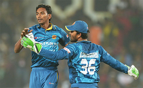 Sri Lanka's Dusmantha Chameera (left) and captain Dinesh Chandimal celebrate after taking the wicket of India's Shikhar Dhawan during the second  T20 international match between India and Sri Lanka at the Jharkhand State Cricket Association International Stadium Complex in Ranchi on February 12, 2016. (AFP)