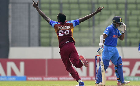West Indies cricketer Chemar K Holder (left) reacts after the dismissal of the Indian cricketer Mahipal Lomror (right) during the under-19s World Cup cricket final between India and West Indies at the Sher-e-Bangla National Cricket Stadium in Dhaka on February 14, 2016.  (AFP)