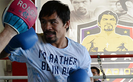 This photo taken on February 15, 2016 shows Philippine boxing legend Manny Pacquiao sparring with his coach Freddie Roach as part of his training at a gym in General Santos City in the southern Philippine island of Mindanao. (AFP)