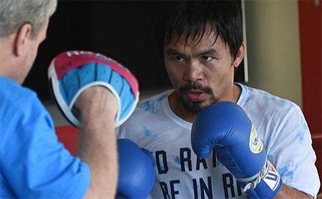 This photo taken on February 15, 2016 shows Philippine boxing legend Manny Pacquiao (R) sparring with his coach Freddie Roach as part of his training at a gym in General Santos City in the southern Philippine island of Mindanao. (AFP)