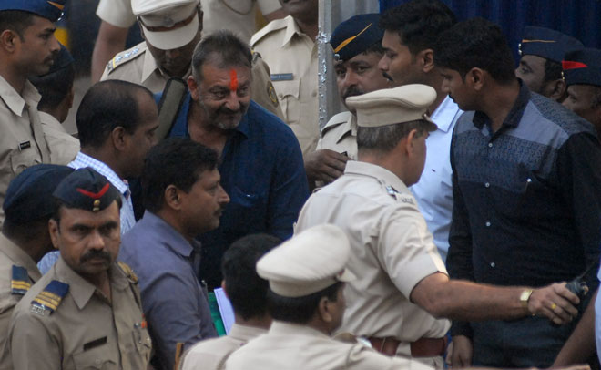 Indian Bollywood actor Sanjay Dutt (C) waves as he is escorted by officials from Yerwada Jail in Pune on February 25, 2016. (AFP)