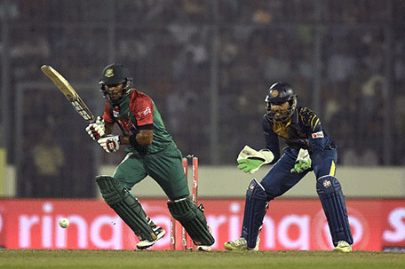 Bangladesh cricketer Sabbir Rahman plays a shot (L) as the Sri Lanka wicketkeeper Dinesh Chandimal (R) looks on during the match between Bangladesh and  Sri Lanka at the Asia Cup T20 cricket tournament at the Sher-e-Bangla National Cricket Stadium in Dhaka on February 28, 2016. AFP