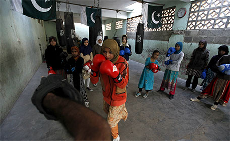 Anum, 17, punches padding with her coach Younus Qambrani while others observe during an exercise session at the first women's boxing coach(Reuters)