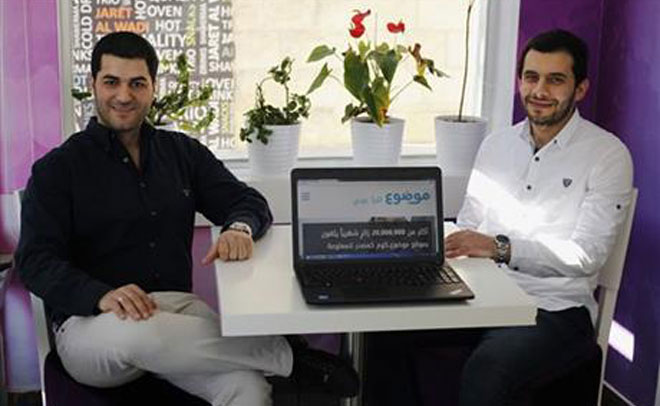 In this Feb. 17, 2016 photo, Mohammad Jaber, left, and Rami Qawasmi, both 27, pose for a portrait with a laptop open to their website Mawdoo3.com, which recently became the largest Arabic content site on the Internet in Amman, Jordan. (AP)