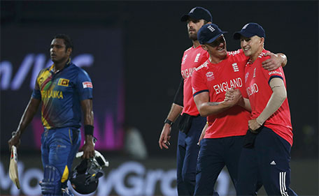 England's players celebrate past Sri Lanka's captain Angelo Mathews (left) as they walk off the field after winning their match. during the World Twenty20 cricket tournament - New Delhi, India, 26/03/2016. (Reuters)