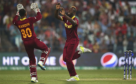 Andre Russell of the West Indies and Denesh Ramdin of the West Indies celebrate after taking the wicket of Alex Hales of England during the ICC World Twenty20 India 2016 Final match between England and West Indies at Eden Gardens on April 3, 2016 in Kolkata, India. (Getty Images)