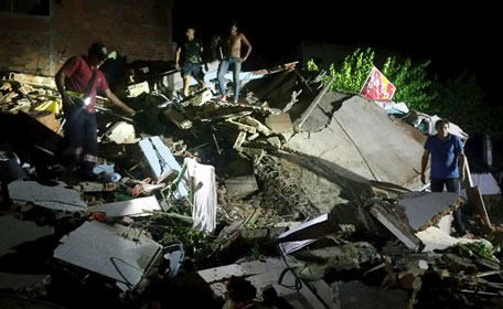 """People stand next to the debris of a building after a 7.8 magnitude earthquake struck off the country's northwest Pacific coast causing """"considerable damage"""", in Manta, Ecuador. (Reuters)"""