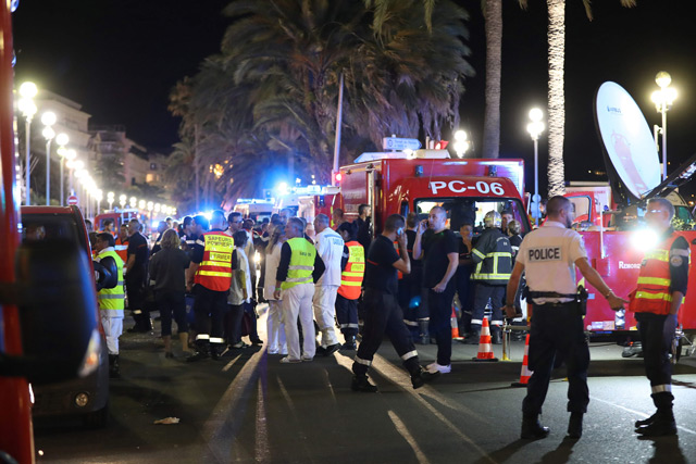 Police officers, firefighters and rescue workers are seen at the site of an attack on July 15, 2016, after a truck drove into a crowd watching a fireworks display in the French Riviera town of Nice. (AFP)