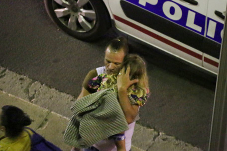 A man holds a child after a truck plowed through Bastille Day revelers in the French resort city of Nice, France. (AP)