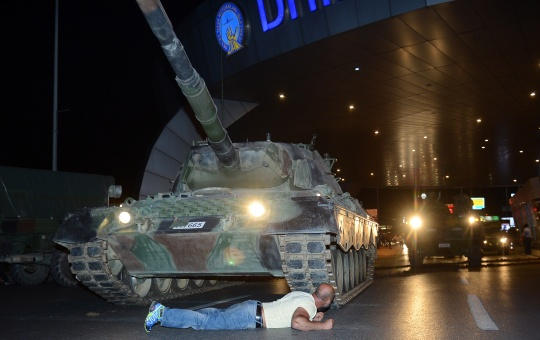 A man lies in front of a tank after Turkish President Tayyip Erdogan urged supporters to take to streets in protest of coup (Reuters)