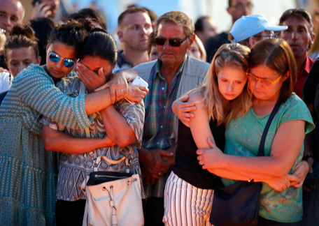 People confort each other as they gather at a makeshift memorial to honor the victims of an attack near the area where a truck mowed through revelers in Nice, southern France, Friday, July 15, 2016. A large truck mowed through revelers gathered for Bastille Day fireworks in Nice, killing more than 80 people and sending people fleeing into the sea as it bore down for more than a mile along the Riviera city's famed waterfront promenade. (AP