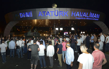 People stand in front of a tank parked in the entrance to Istanbul's Ataturk airport, early Saturday, July 16, 2016. (AP)