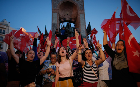 People chant slogans as they gather at a pro-government rally in central Istanbul's Taksim square, Saturday, July 16, 2016. Forces loyal to Turkish President Recep Tayyip Erdogan quashed a coup attempt in a night of explosions, air battles and gunfire that left some hundreds of people dead and scores of others wounded Saturday. (AP)